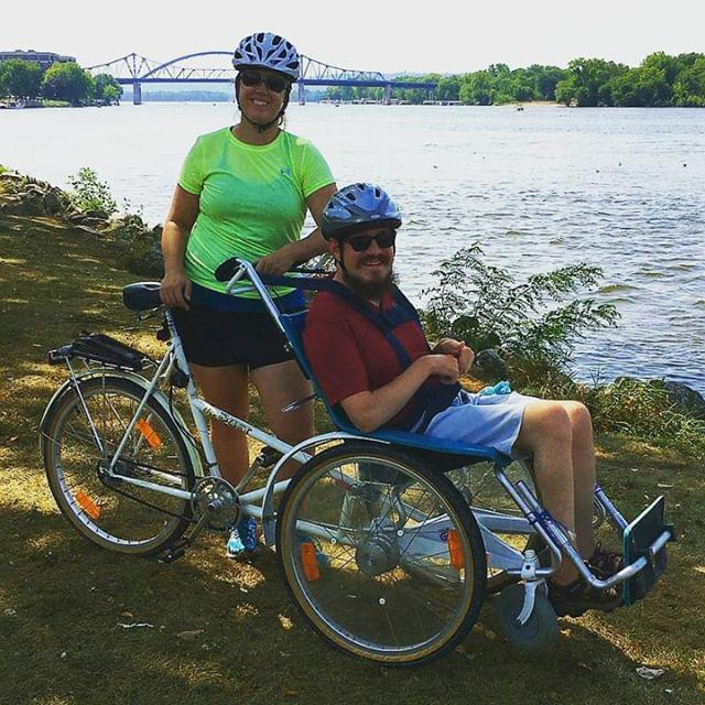 A couple using an assisted wheelchair bike. A river and bridge in the background.