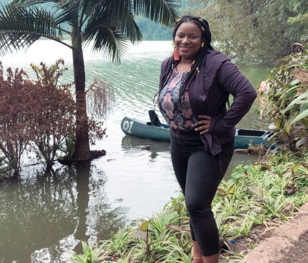 Aprili stands smiling with hands on hips. A canoe on the water in background.