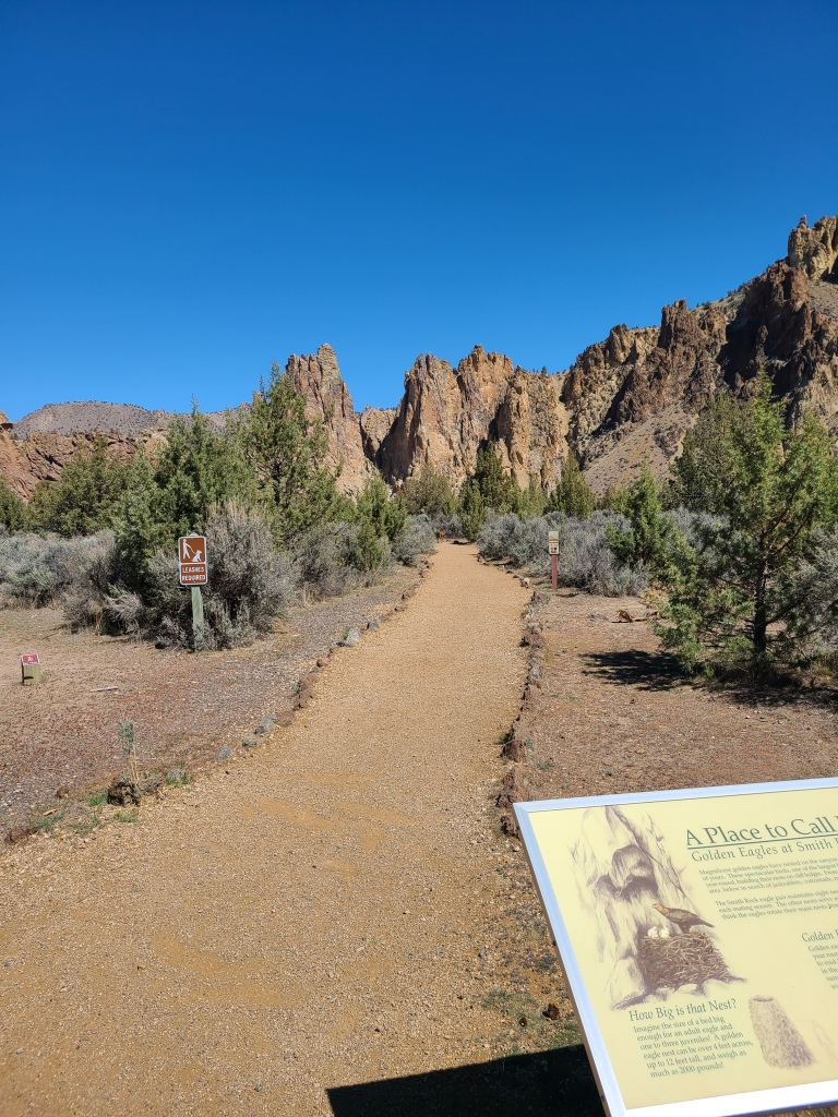 North Point gravel trail travels through sage and small juniper trees. Tall rocks rising in the background.