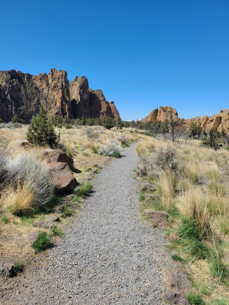Beginning on the Rim Rock Trail. Pea gravel surface travels among grass and sage with cliffs in the background.