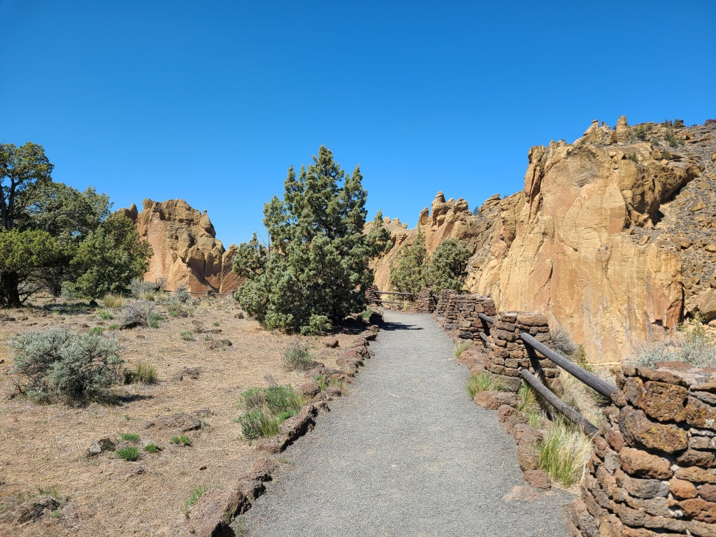 Viewpoint along the Rim Rock Trail. Gravel surface with wood and rock barrier on the right, cliffs rising along the opposite edge