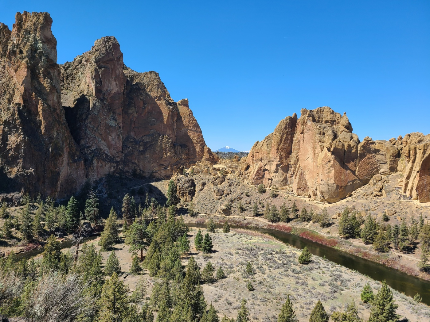 View from an overlook at Smith Rock State Park.River flowing through a canyon, tall cliffs rising above, a mountain in the background.